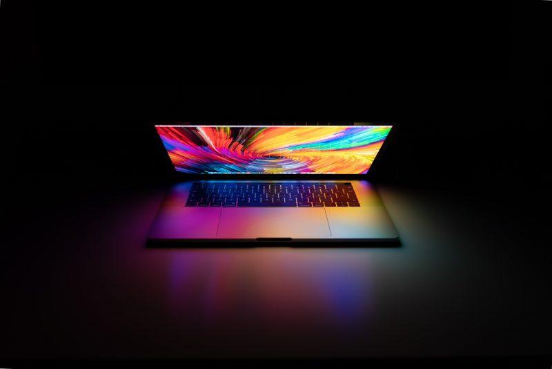 A laptop emitting blue light in the dark