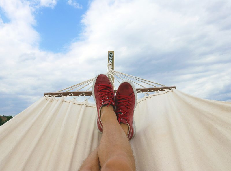 The legs and feet of a man on a hammock with the blue sky behind
