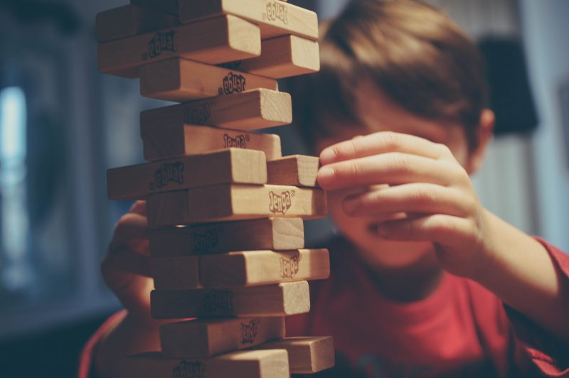 A boy builds the wooden blocks on a Jenga tower