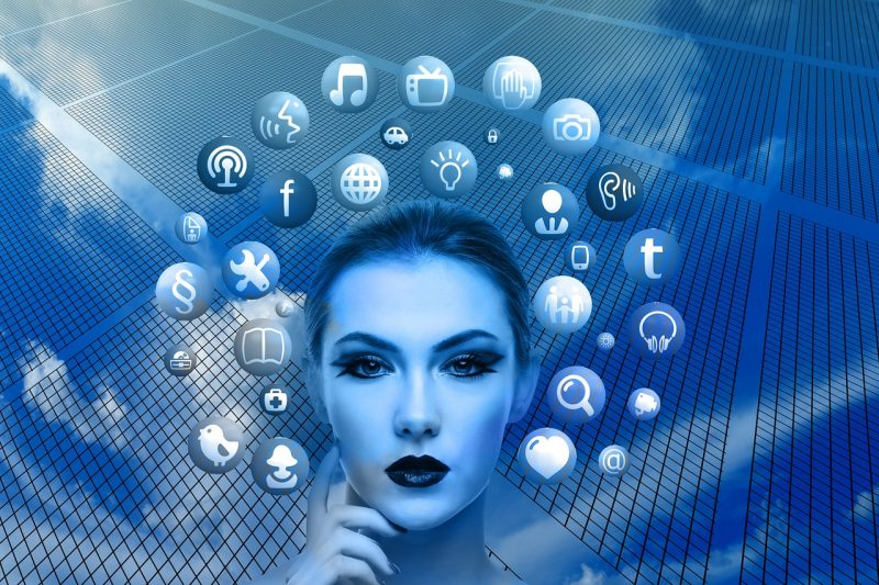 An illustration of a woman's head with social media icons flying around it