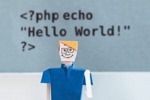 "A paper doll in front of a wall that says ""Hello World!"""